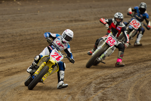 Photo of three dirt bike racers turning a corner of a track during a race